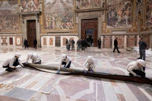 Los mozos desenrollan en el suelo un tapiz